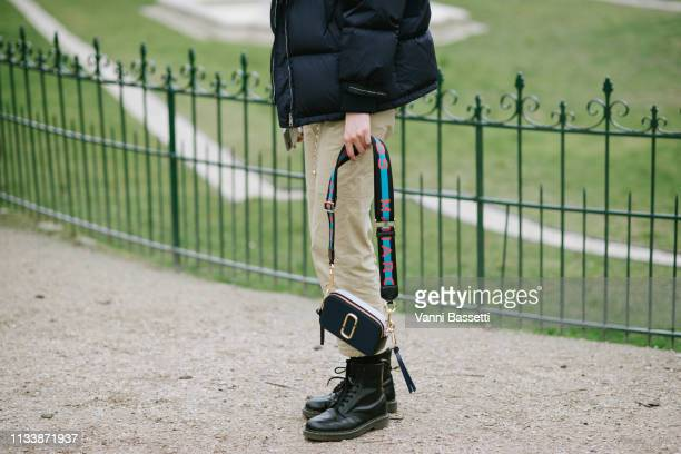 A model poses wearing a Prada down jacket Dr Martens shoes and Marc Jacobs bag after the Chanel show at the Grand Palais during Paris Fashion Week...