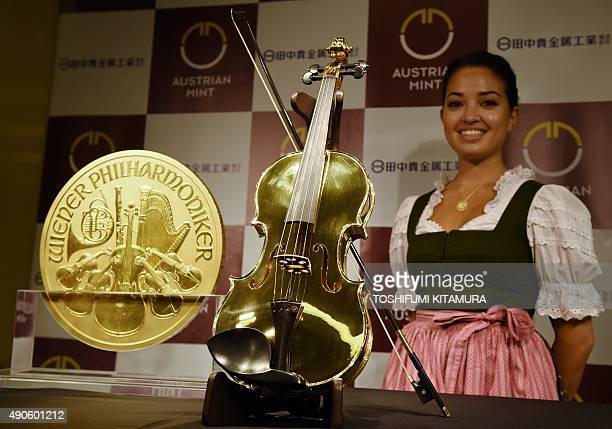 A model poses with a 14kilogram gold violin and a 2004 1000ounce Vienna Philharmonic gold bullion coin during a press preview at the Ginza Tanaka...