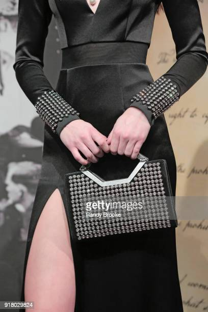 A model poses with a black and silver studded purse and matching dress sleeves at the Alice Olivia By Stacey Bendet Presentation February 2018 New...
