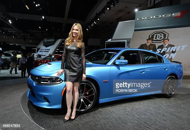 A model poses with a Dodge Charger at the Los Angeles Auto Show November 19 2014 in Los Angeles California AFP PHOTO / ROBYN BECK