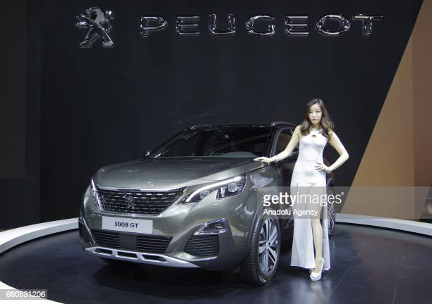 A model poses with a Peugeot 3008GT during the Seoul Motor Show 2017 at KINTEX in Seoul South Korea on March 30 2017