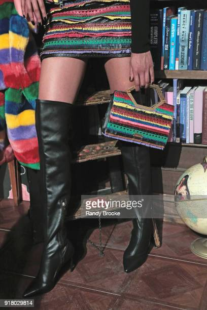 A model poses with a rainbow colored handbag and knee high black boots at the Alice Olivia By Stacey Bendet Presentation February 2018 New York...