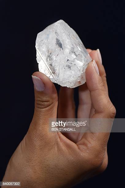 A model poses with an uncut 1109carat diamond named 'Lesedi La Rona' estimated to realise in excess of 70 million USD at Sotheby's auction house in...