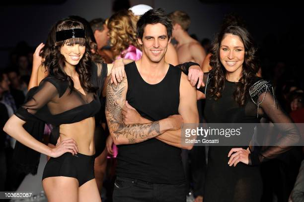A model poses with Mitchell Johnson and Giaan Rooney on the catwalk during the Hot In The City Intimates group show as part of Rosemount Sydney...
