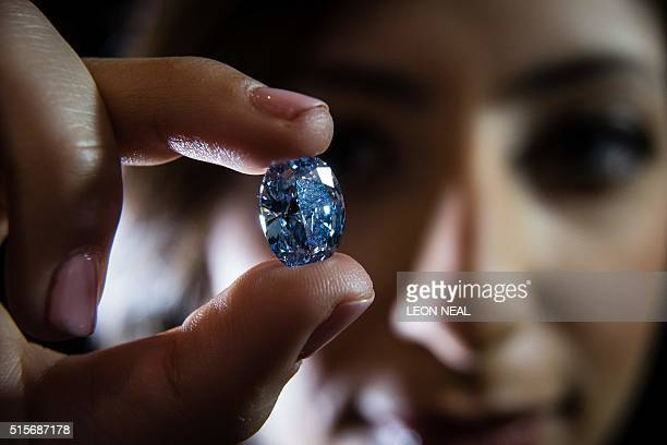 Model poses with the De Beers Millennium Jewel 4, a rare Oval Internally Flawless Fancy Vivid Blue Diamond weighing 10.10 carats the largest oval...