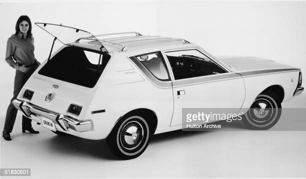 A model poses with the fourpassenger 1970 AMC Gremlin with rear liftgate and rooftop luggage rack a twodoor subcompact car measuring only a fraction...