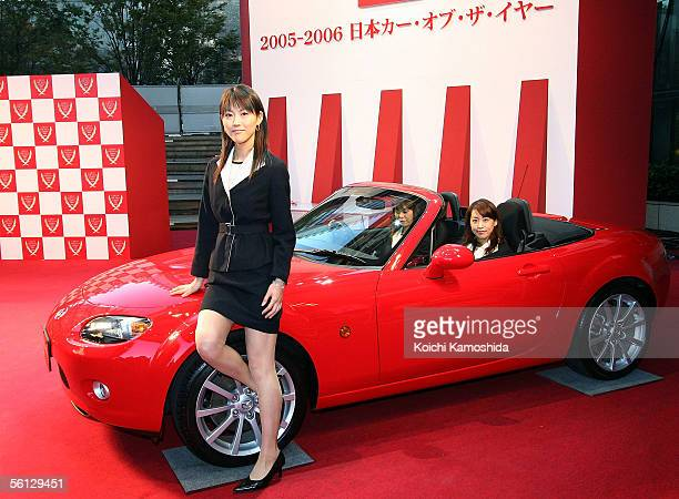 A model poses with the Mazda Roadster sports car also known as the MX5 during the Car of the Year Japan awards November 9 2005 in Tokyo Japan The...