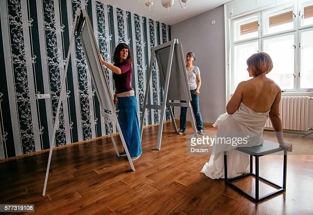 Model posing in European studio to two female artists
