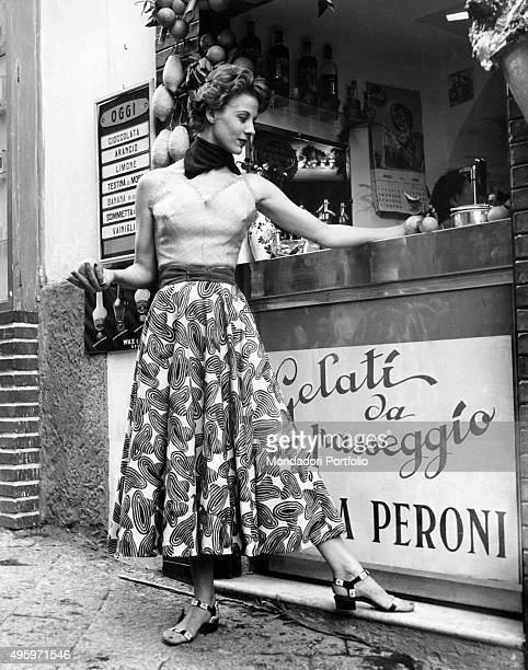 A model posing in front of an ice cream kiosk in a dress designed by the fashion house Antonelli Italy 1955