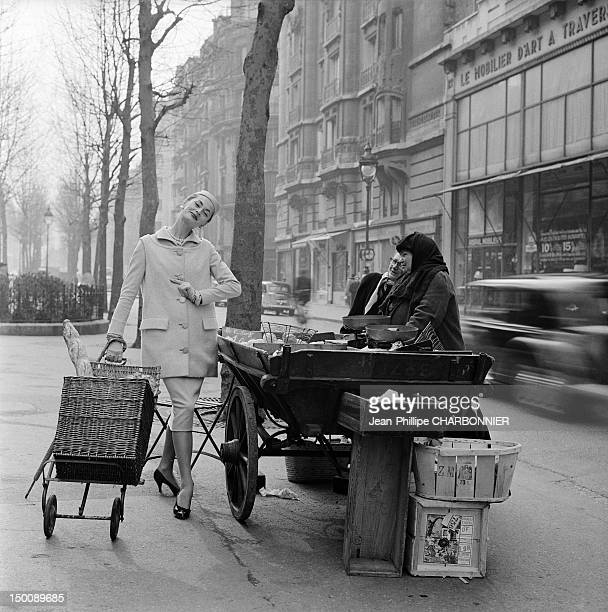 Model posing in the street in front of a vegetable stallholder 1960 in Paris France