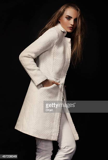 Model posing in white trench coat on black background