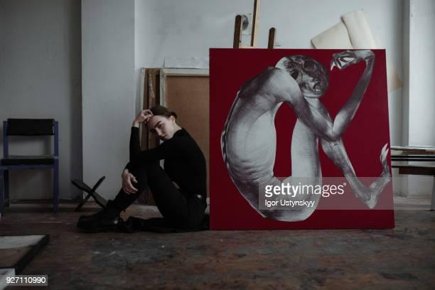 Model posing next to her art