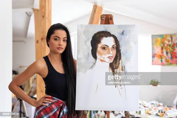 Model posing next to her portrait
