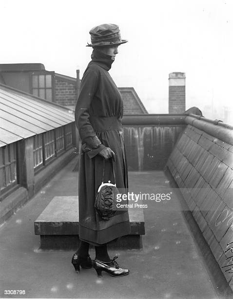 A model posing on a rooftop and wearing a ruchedwaist suit from Burberry's London with fur collar and gauntlet gloves