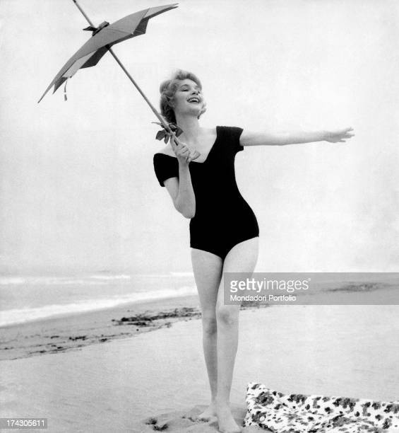 A model posing on the seashore wearing a black swimsuit and holding a parasol in her hand 1959