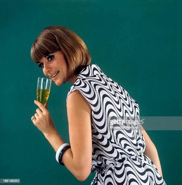 A model posing smiling and holding a cocktail glass 1966
