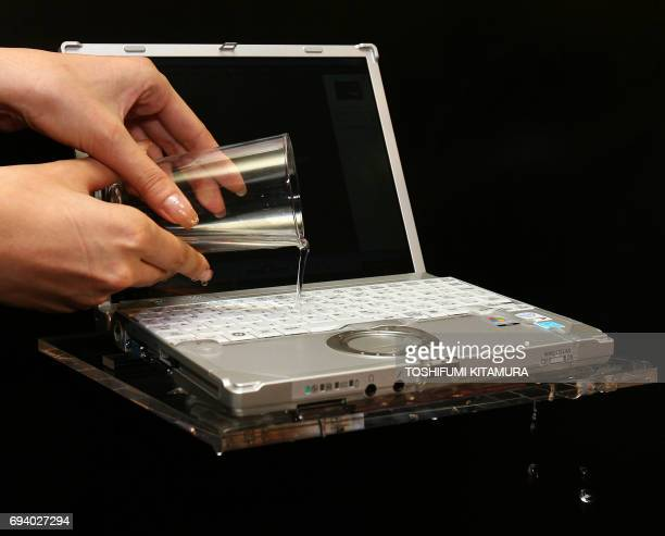 A model pours a glass of water onto a keyboard during a water proof demonstration of the applicationrunning Panasonic CFR6 notebook PC in its press...
