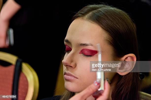 A model prepares backstage at the Apu Jan show during London Fashion Week Fall/Winter 2015/16 at Fashion Scout Venue on February 21 2015 in London...