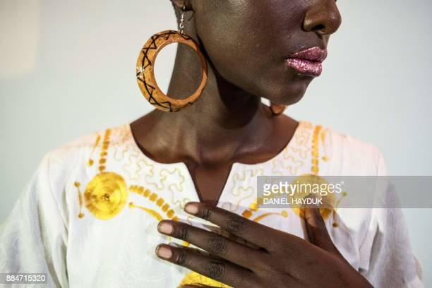 A model prepares backstage before showcasing a creation by South of Sahara during the 10th Swahili Fashion Week in Dar es Salaam Tanzania on December...