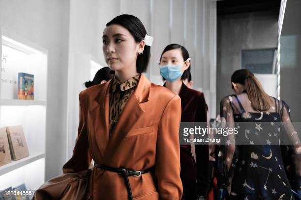 A model prepares backstage before the Larome DIANA KWAN collection show by Chinese designer Yifan ChenYue Guan during the China Fashion Week...