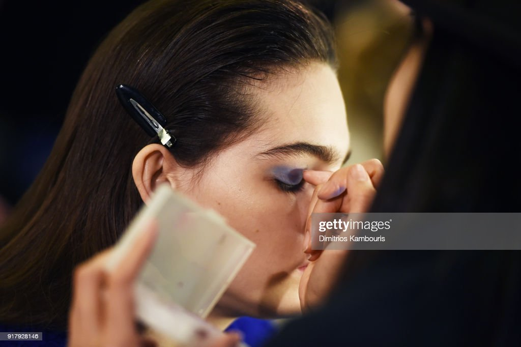 A model prepares backstage for BOSS Womenswear during New York Fashion Week at Cedar Lake on February 13, 2018 in New York City.