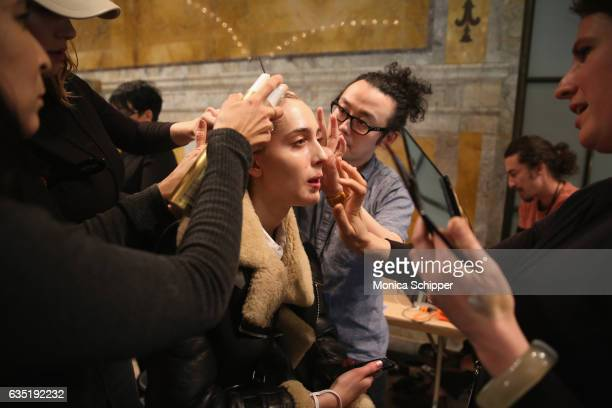 A model prepares backstage for the Philipp Plein collection during New York Fashion Week The Shows at New York Public Library on February 13 2017 in...