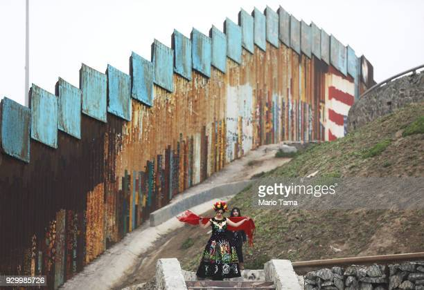 A model prepares for a photo shoot along the USMexico border fence while standing on the Mexican side of the fence in Tijuana's beach district on...