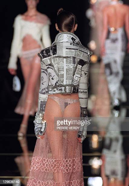 A model presents a Christian Dior Daily newspaper inspired jacket with pink champagne transparent skirt by John Galliano for Christian Dior during...