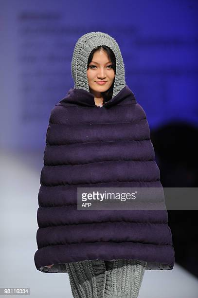 Model presents a creation by a young Chinese designer during a presentation by various design universities in Beijing on March 26, 2010. The...