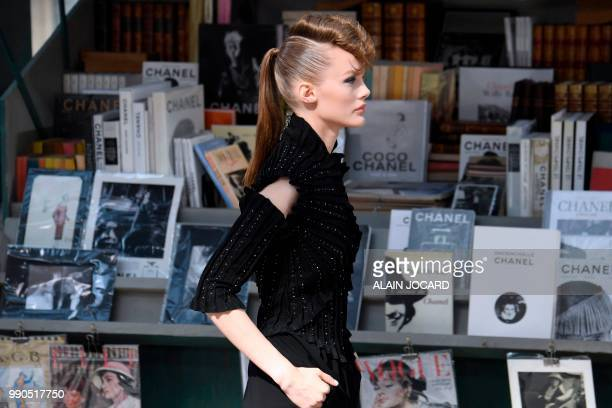 A model presents a creation by Chanel along a replica of Parisian openair book stalls at the Grand Palais in Paris during the 20182019 Fall/Winter...