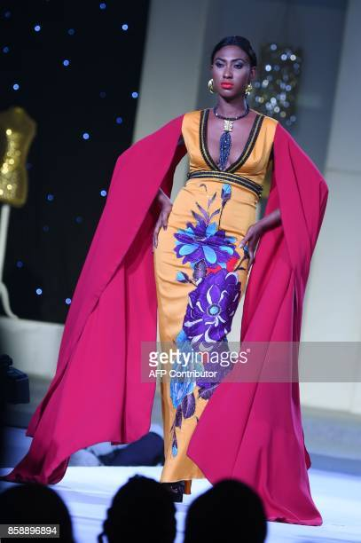 A model presents a creation by designer KORO DK during the Africa Fashion show on October 7 2017 in Abidjan / AFP PHOTO / SIA KAMBOU
