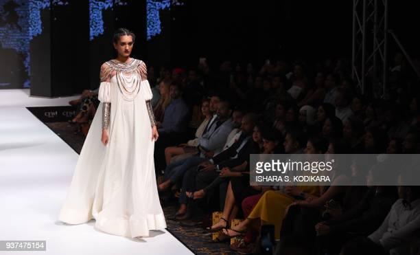 A model presents a creation by fashion designer Dimuthu Sahabandu during the Colombo fashion week on March 24 2018 / AFP PHOTO / ISHARA S KODIKARA