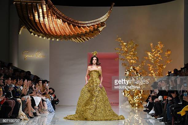 TOPSHOT A model presents a creation by Guo Pei during the 2016 spring/summer Haute Couture collection on January 27 2016 in Paris / AFP / MIGUEL...