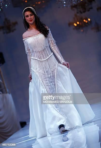 A model presents a creation by Saudi Arabia fashion designer Rana Riri during the Gulf's Forum of Elegance event on December 21 2014 in the Omani...