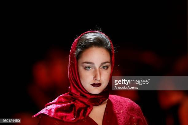 A model presents a creation by Slava Zaitsev during the MercedesBenz Fashion Week in Moscow Russia on March 10 2018