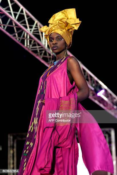 A model presents a creation during Dakar Fashion Week on June 29 2017 in Niari Taly a popular neighborhood in the Senegalese capital where the...
