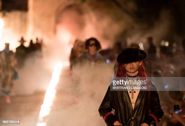 A model presents a creation for Gucci during the 2019 Gucci Croisiere collection fashion show on May 30 2018 at Alyscamps in Arles southeastern France