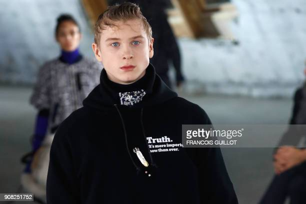 TOPSHOT A model presents a creation for Japanese brand Sacai by designer Chitose Abe bearing the lines 'Truth It's more important now than ever'...