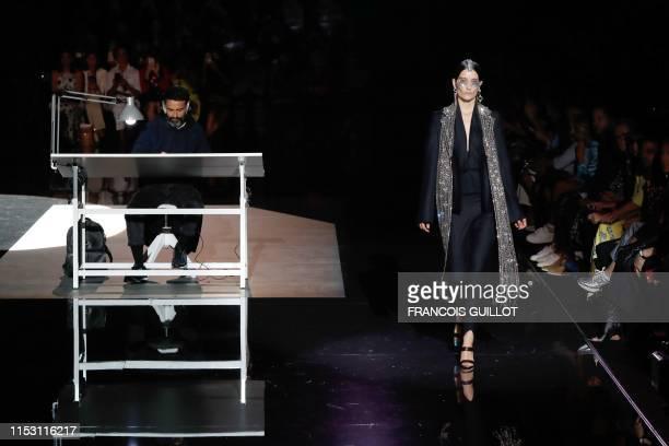 A model presents a creation next to fashion designer for Schiaparelli Daniel Roseberry during the Women's FallWinter 2019/2020 Haute Couture...