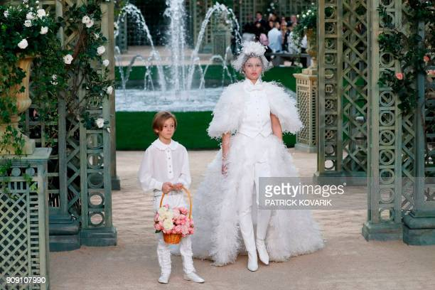 A model presents a creation with Karl Lagerfeld's godson Hudson Kroenig for Chanel during the 2018 spring/summer Haute Couture collection fashion...