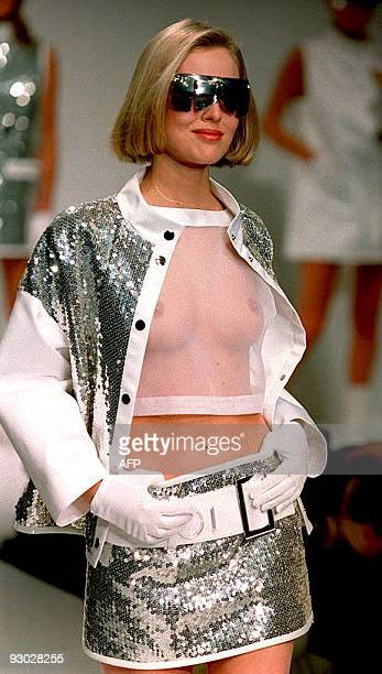 A model presents a jacket and mini skirt in silver sequins over a short organza Tshirt during the Courreges 1994/95 Fall/Winter ready to wear...