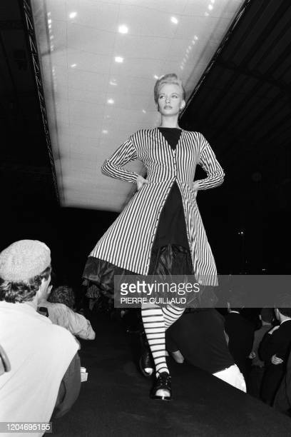 A model presents an evening ensemble composed with a black and white stripped fitted coat covering a black linen and taffeta fullness dress tights...