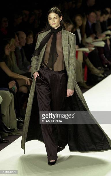 A model presents an outfit of a sheer top under a floorlength plaid coat during the Ralph Lauren fashion show 09 February in New York The show is...