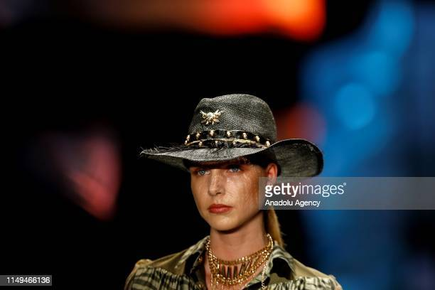 Model presents hat on runway at Dosso Dossi Fashion Show in Antalya, Turkey on June 12, 2019.