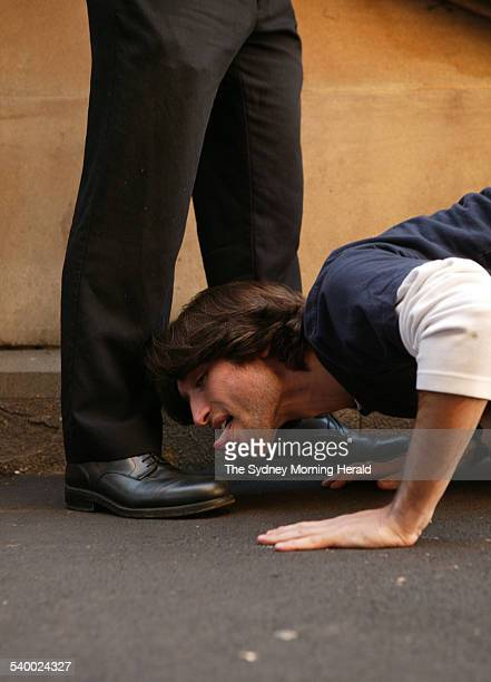 A model pretends to grovel at the feet of a businessman by licking his shoe 13 June 2006 SMH Picture by MARCO DEL GRANDE