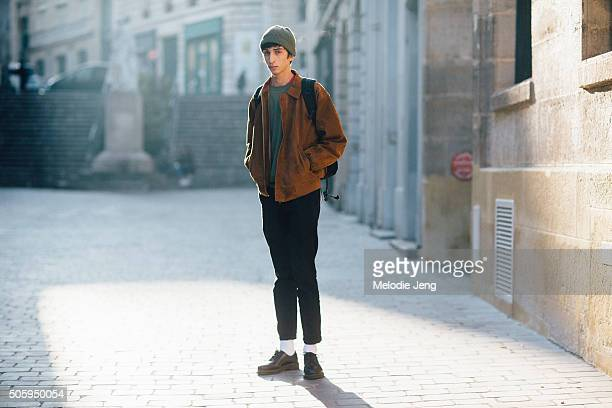 Model Raad at Tomorrow is Another Day agency exits the Lemaire show in a green beanie brown suede bomber jacket green shirt black jeans and shoes on...