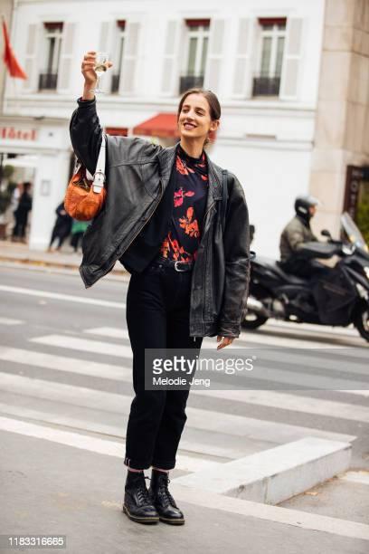 Model Rachel Marx cheers with champagne and wears a black leather jacket, black/red floral Dries Van Noten top, brown vintage Coach bag, black pants,...