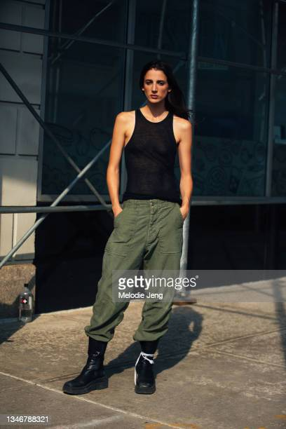 Model Rachel Marx wears a black tanktop, green military-style pants, and black boots after the Altuzarra show on September 12, 2021 in New York City.