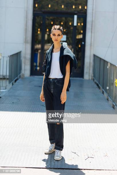 Model Rachelle Harris wears a sweatshirt on her shoulders, white top, black jeans, and camouflage Converse sneakers after the Elie Saab show during...