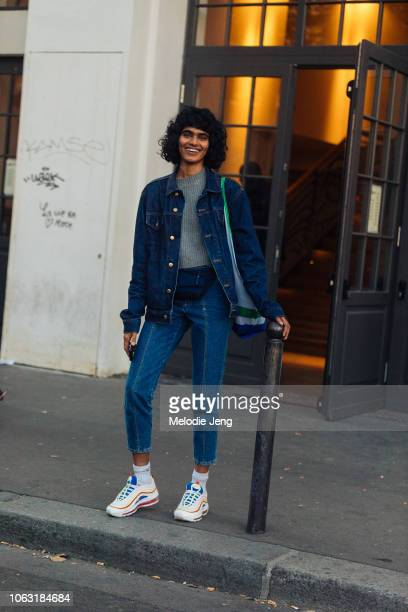 Model Radhika Nair wears a denim jacket, black fanny pack, jeans, and white Nike sneakers after the Lemaire show during Paris Fashion Week...
